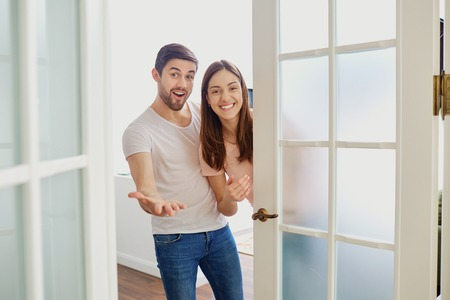 A happy couple with smiles opens the door to their house.