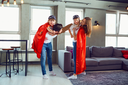 A happy family plays in superheroes indoors. Banco de Imagens