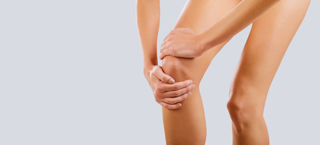 Pain, injury to the knee. A woman holds her knee with her hand. Standard-Bild