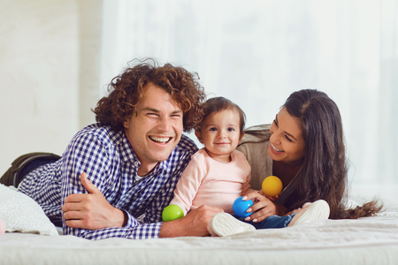 Happy family playing with the baby in the room. Young mother and father play with the daughter on a bed indoors.