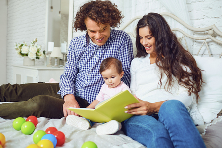 Happy family is reading a book with a child in the room. Young mother and father teach daughter to read indoors.