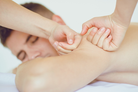Back massage for a man lying on the table in the spa salon.