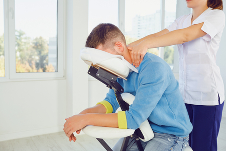 Massage on the massage chair in the office. Masseur does massage to a man sitting on a massage chair in a clinic. Stock Photo