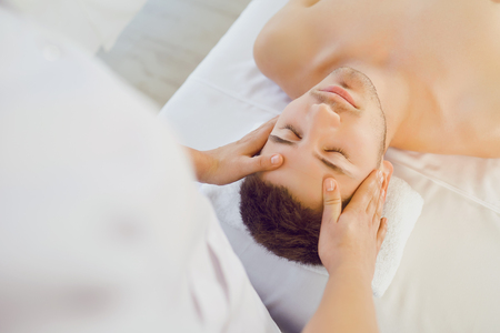 Facial massage for man. Hands of the massage therapist make a relaxing face massage to a man in a massage room. Zdjęcie Seryjne