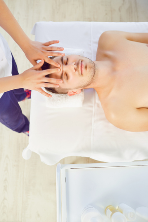 Facial massage for man. Hands of the massage therapist make a relaxing face massage to a man in a massage room. Stock Photo