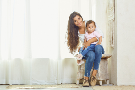 Mother brunette plays with the child at home. Mothers day. Stock Photo
