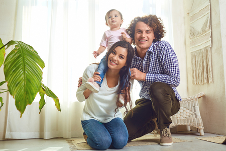 Happy family playing with baby at home. Mother, father and daughter play together in a room.