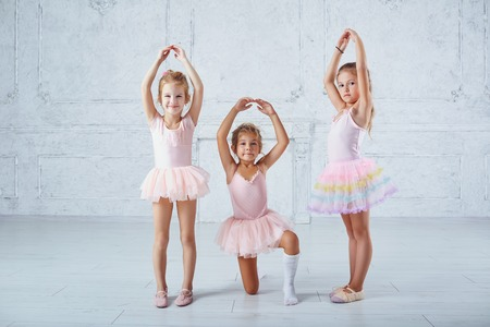 Children girls in ballerina costumes are engaged in dancing in a dance school.