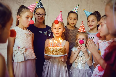 Children with a birthday cake have fun at a birthday party.