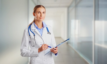 Doctor blonde in lab coat in the clinic on the background for text. Stock Photo
