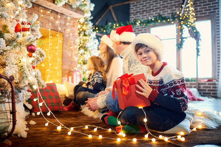 Family playing with gifts on the floor indoors on Christmas Day. Stock Photo