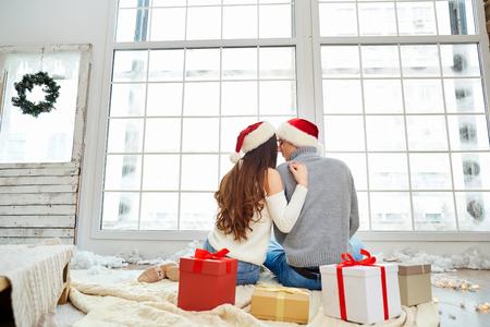 Happy young couple wearing Santa hats having fun at Christmas.