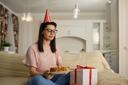 An unhappy girl wearing a hat on her birthday with a cake with candles is alone in the room.