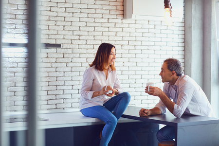 Mature couple with cup of coffee happy hugging indoors.