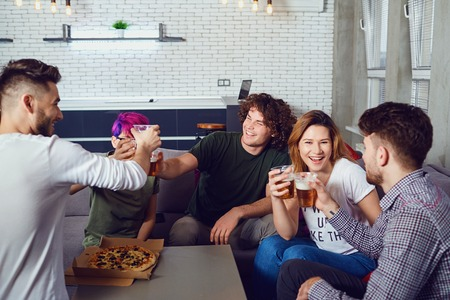 A group of friends is clinking glasses with beer in the room. Stock Photo
