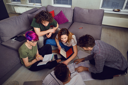 A group of young people students are discussed indoors.