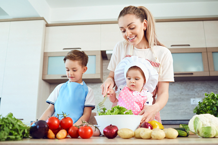 Mother and children are cooking in the kitchen.