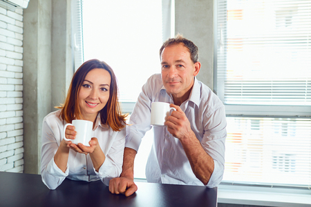A couple of middle-aged people with mugs in their hands indoors in the background of a window.
