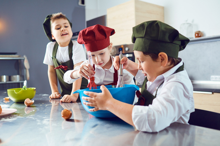 A group of children are cooking at the table in the kitchen.