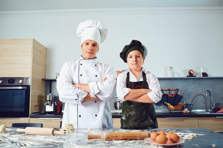 Cook with the boy in the uniform of the cook in the kitchen with the dough. Stock Photo