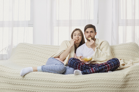 A young couple sitting on the couch watching an interesting TV eating popcorn.