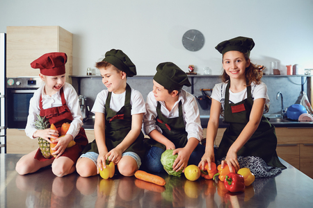 Funny children in the uniform of cooks on the table in vegetables in the kitchen.