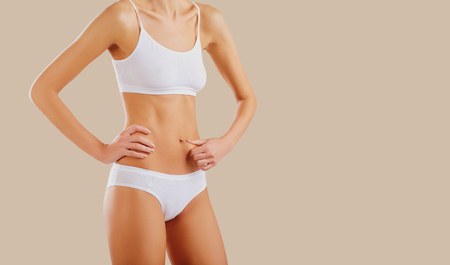 The body of a thin slim woman with a beautiful figure. The concept of losing weight and diet.