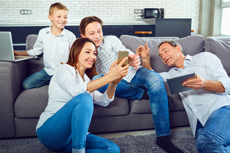 A happy family with a laptop is having fun in the room. Stock Photo