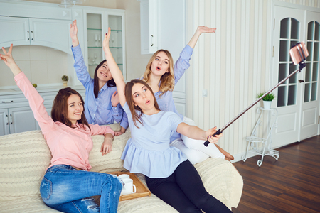 A group of young girls friends do selfie on the phone at a meeting in a room indoors.