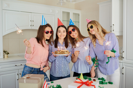 A group of girlfriends with a cake with candles celebrate a birthday inside the room.