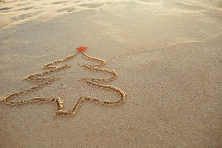 The concept of Christmas. Painted Christmas tree in the sand on the beach. Stock Photo