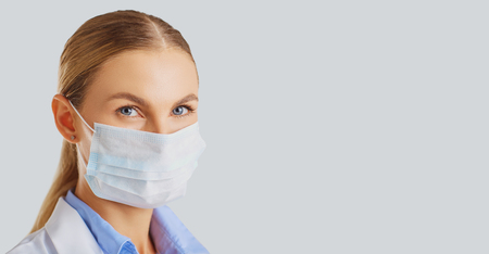 Woman doctor wearing a mask against a gray background .