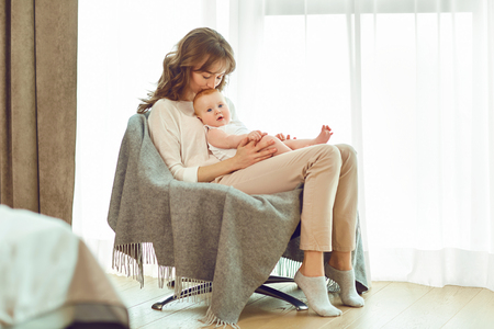 A mother with a baby in her arms sitting on a chair in front of a window in the room. 스톡 콘텐츠