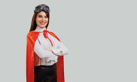 Cheerful woman wearing red cloak with aviator goggles holding arms crossed on gray background Stock Photo