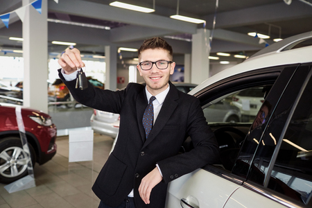 Smiling young man in glasses and suit leaning confidently on new car holding keys and looking at camera