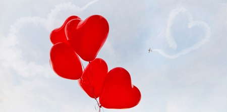 Red balloons against the sky with heart simbol a flying airplane.