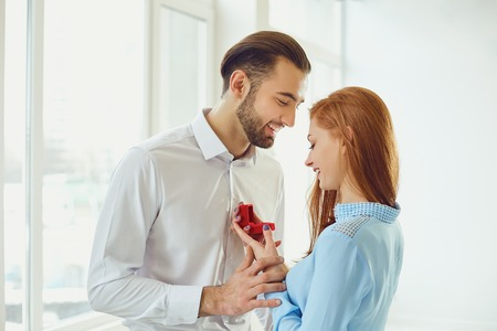 Man proposes to a girl in a white room with bright windows.
