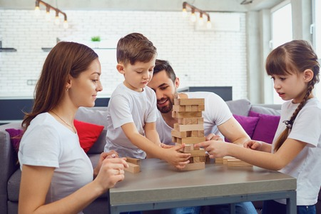 Happy family playing board games at home. Mother, father and children play together.