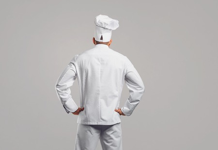 Chef cook in white uniform standing back view on gray background .