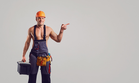 Sexy repairman in helmet smiling at the special clothes with a working tool on a gray background. 版權商用圖片 - 117262429