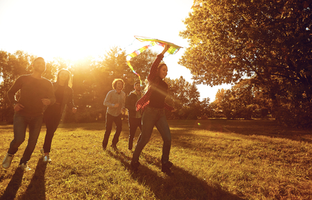 Group of excited young people with colorful kite running together on lawn in park in sunset time