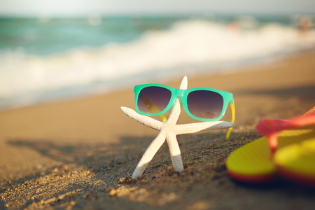 Summer holiday concept. Starfish and sunglasses on the sand of the sea beach. Imagens