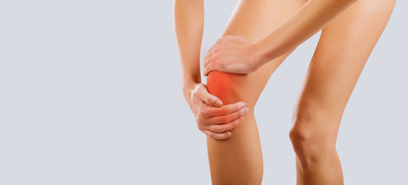 Pain, injury to the knee. A woman holds her knee with her hand. Фото со стока