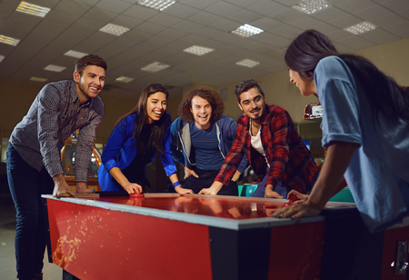 A group of friends playing air hockey in an amusement park. Young people have fun.