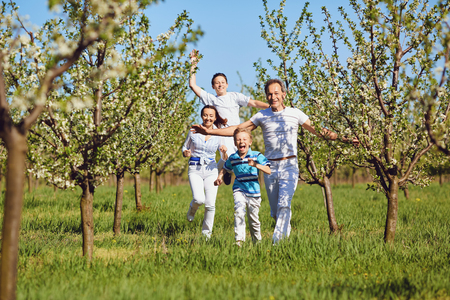 Happy family running in the park in the summer, in the spring. Stockfoto
