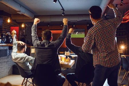 Friends watch sport tv in the pub. Young people support their team in the bar.