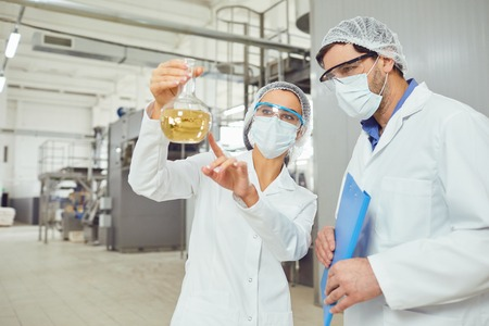 Workers in masks and coats look at the liquid in the flask at work. Stock Photo