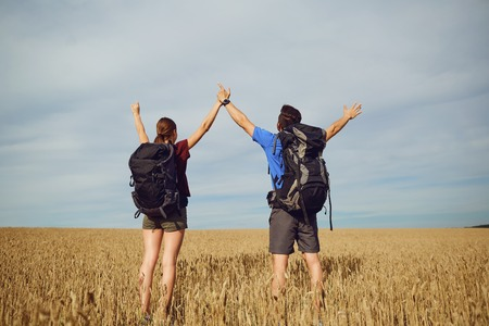 Happy couple of tourists with backpacks raised their hands up in nature. Back view.