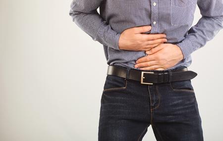 Un homme souffre de douleurs abdominales. Douleur abdominale. Le gars dans les vêtements apparents tenant le ventre avec les mains.