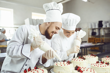 A confectioners squeezes liquid cream from a pastry bag in confectionery . Two pastry chefs work in the bakery.
